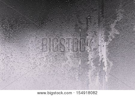abstract background and brilliant texture of graphite color of wet glass with drops of water and with frost or with hoarfrost