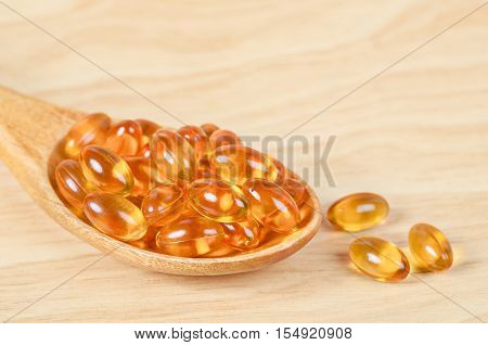 Cod liver oil omega 3 gel capsules in wooden spoon on wooden background.