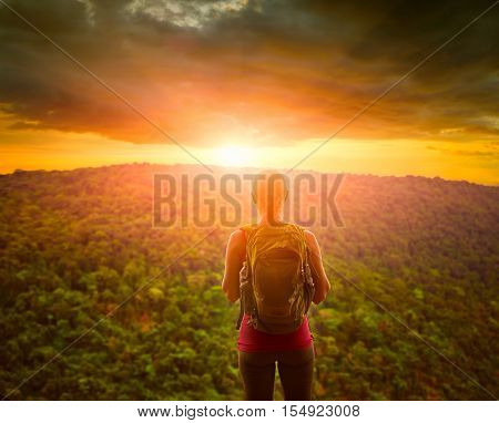 Travelling woman with backpack looking green mountains and inspiring sunset with dramatic clouds. Tourist girl traveling along Asia active lifestyle concept