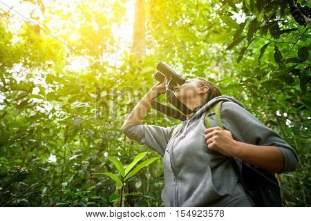Tourist looking through binoculars considers wild birds in the jungle. Bird watching tours