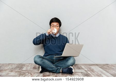 Asian man with laptop and cup. sitting down