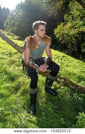 Young medieval archer with chain shirt sits on branch in the Nature in the sunlight