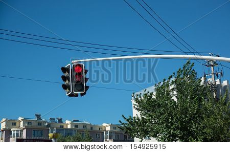 Traffic light showing red signal and time counter. Traffic light hanging over the road with buildings on background.