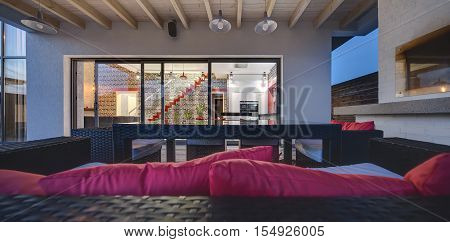 View from the terrace at the glowing hall in a modern style with a kitchen zone, a red stair and dark brick walls. On the terrace there are wicker furniture with red pillows and a brick furnace.