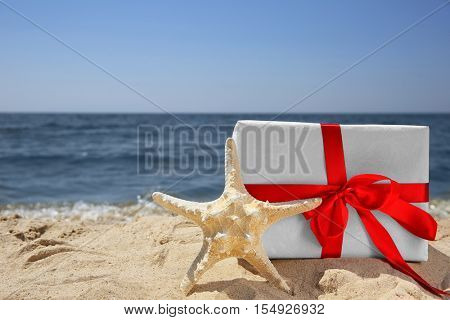 Gift box with sea star on beach. Christmas holiday concept
