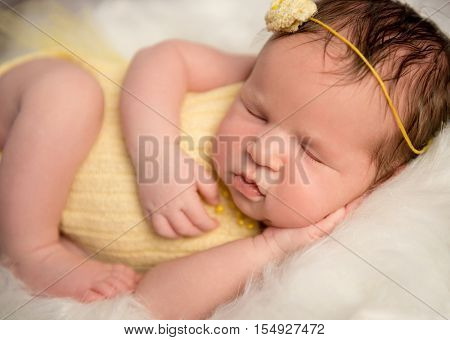 lovely newborn baby in yellow romper and headband sleeping with legs crossed