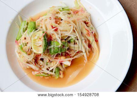 Green Papaya Salad (som Tum Thai) In White Dish On Wood Table, Thai Cuisine Spicy Delicious