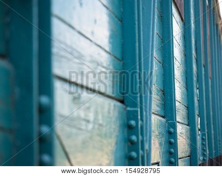 Picture of the wooden wall painted with turquoise blue colour. Old paintwork on the wall. An old country house made of planking. Background of the wooden wall.