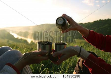 Clink glasses a cup of tea in the morning at sunrise two people drinking tea and clink cups from a thermos on the nature