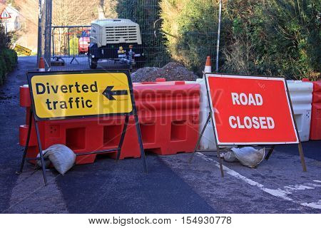 Closed road with diversion signs and barrier