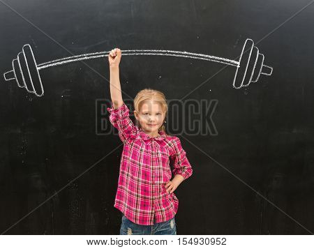 cute little girl rising up drawn on the blackboard barbell with one hand