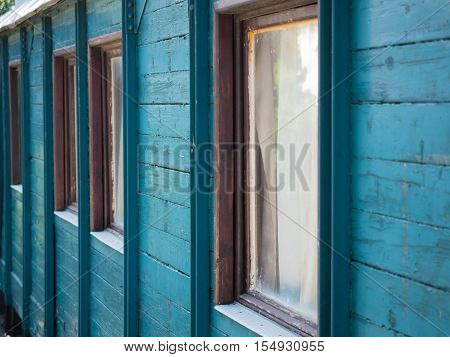 Picture of the wooden wall painted with turquoise blue colour. Old paintwork on the wall. An old country house made of planking. Brown window frames in the wooden country house.