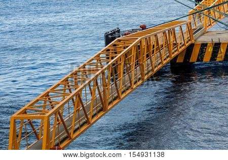 Yellow metal girder bridge across water at port