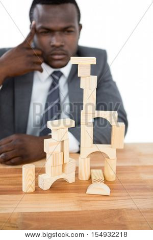 Thoughtful businessman building tower of wooden blocks
