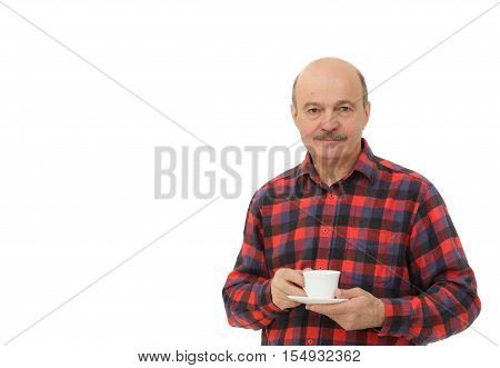 elderly bald man with a mustache takes a sip of coffee from a white mug.