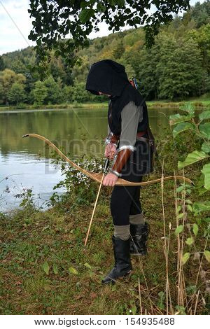 Medieval archer with black hood with the curve span before a lake and looks down
