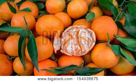 One peeled tangerine on the background of tangerines. Tangerines for sale. Horizontal. Daylight.