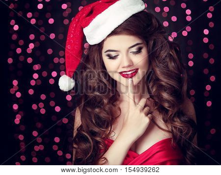Surprised Santa Girl With Finger On Lips. Beautiful Smiling Woman Model In Red Hat Over Christmas Pa