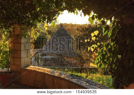 Italy landscape: Apulia countryside. Valle d'Itria, territory of Cisternino. Hills with olive trees and Trullo.Typical example of rural Apulian landscape.Portico overlooking landscape at sunset.