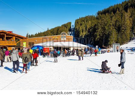Bansko, Bulgaria - December 12, 2015: Bunderishka polyana, ski station, cable car lift, Bansko, Bulgaria,  blue cabins and mountain with pine trees, people