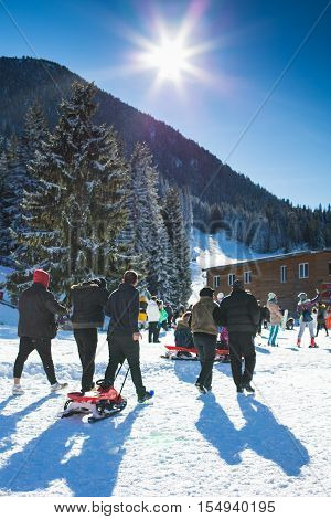 Bansko, Bulgaria - December 12, 2015: Ski resort Bansko, Bulgaria, bright sun and mountain with pine trees, people walking with sledge