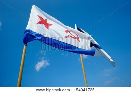 Two flags on background of blue sky. Naval flag of the USSR - red star, hammer and sickle. And Naval flag of Russia. Sevastopol. Crimea poster