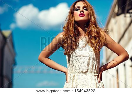 High fashion look.glamor beautiful sexy stylish blond young woman model with bright makeup and pink lips with perfect clean skin in white summer dress in the city behind blue sky