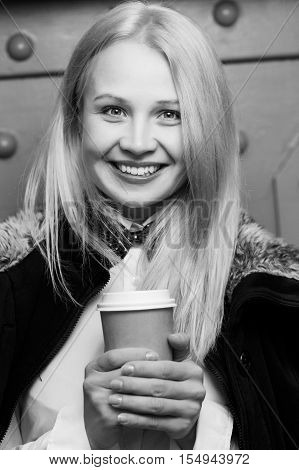 Beautiful smiling girl holding paper cup of coffee, black and white photo