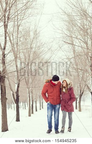 Loving couple walking in the snow enjoying the winter holidays