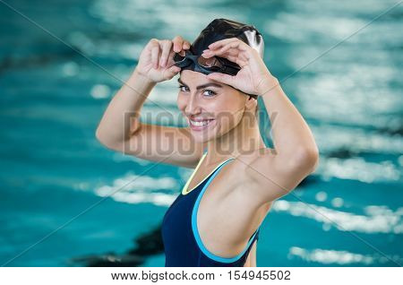 Portrait of fit young woman wearing swimming cap and goggles at the pool. Portrait of a smiling female swimmer wearing swim goggles at swimming pool. Happy fit girl at pool looking at camera.