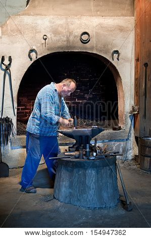 Ruzomberok Slovakia - June 30 2012: Blacksmith working metal on the anvil in the forge. Metal products handmade in the workshop