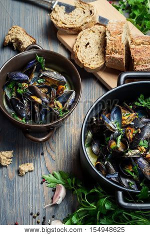 Fresh ingredients to prepare mussels on old wooden table