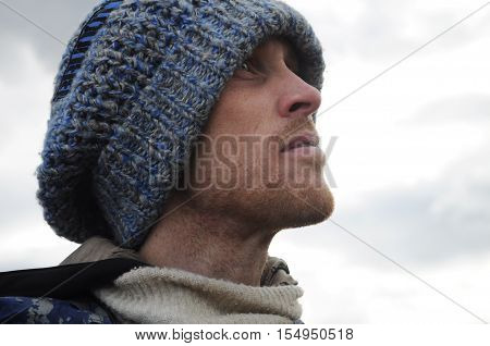 cute portrait of a man in a hat looks into the distance on the nature