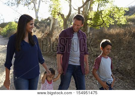 Mixed race family walking on rural path, backlit front view