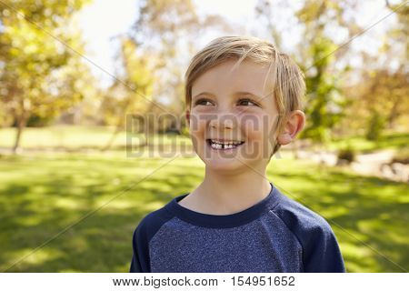 Seven year old Caucasian boy in park looks away from camera