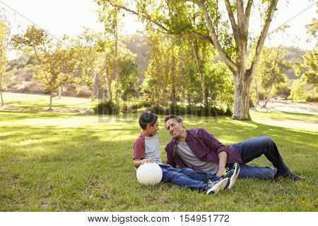 Father and son relaxing with soccer ball in a park