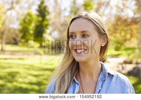 Mid thirties white woman looking away from camera in park