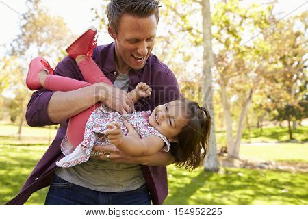 Dad cradling toddler daughter in his arms at the park