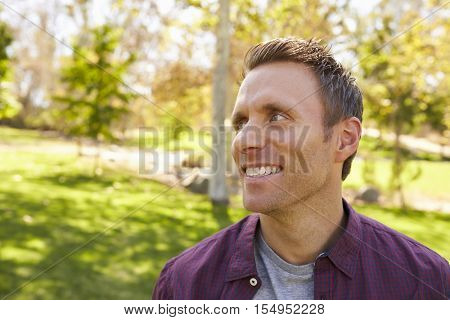 Happy adult man in park looking away from camera, close up