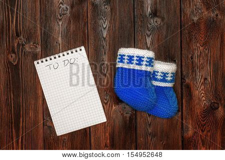Blue hand made crochet baby booties and blank notebook with todo list, on wooden background, copyspace