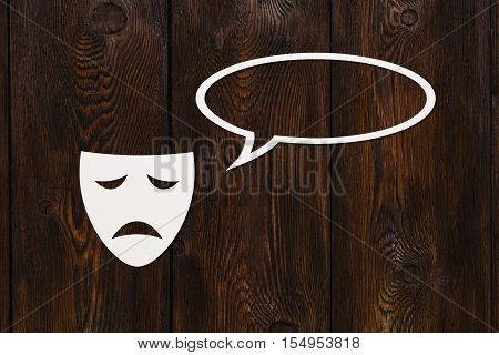Paper sad mask is talking. Conversation. Emotion concept. Dark wooden background. Abstract conceptual image with copyspace