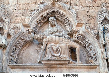 DUBROVNIK, CROATIA - NOVEMBER 29: Statue of Our Lady of Sorrow on the portal of the Franciscan church of the Friars Minor in Dubrovnik, Croatia on November 29, 2015.