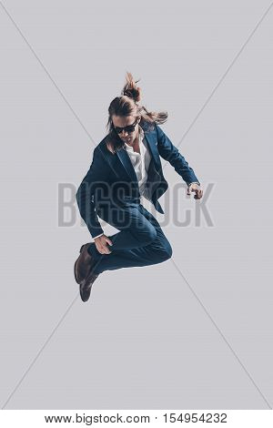 Mid-air style. Handsome young man in full suit jumping against grey background