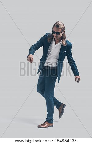 Style in motion. Full length of handsome young man in full suit posing against grey background