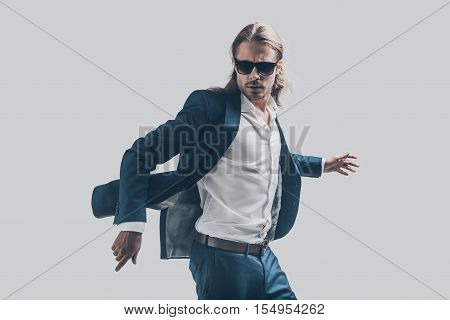 His perfect style in motion. Handsome young man in full suit moving in front of grey background