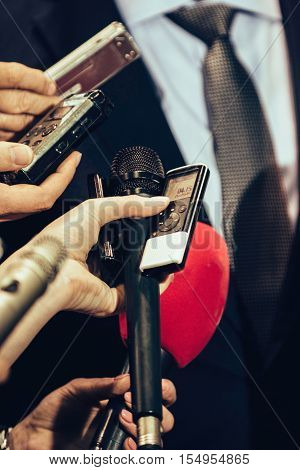 Journalists interviewing politician on public event, toned image