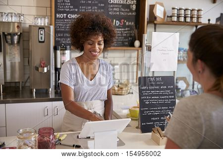 Waitress taking a customers order at till in a coffee shop