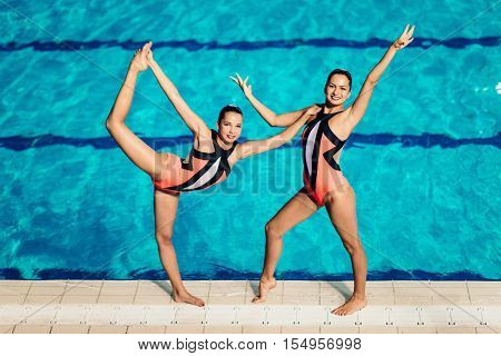 Synchronized Swimmers by the pool, toned image, horizontal