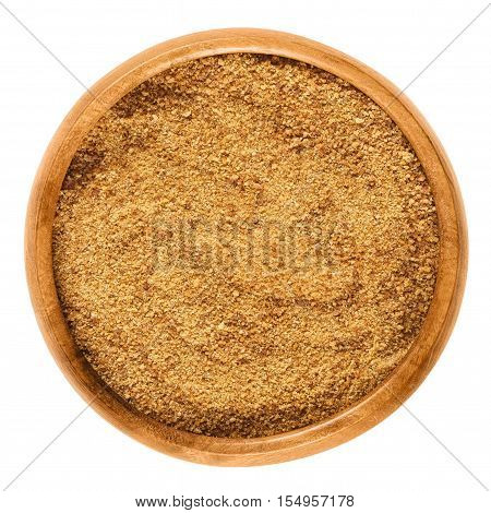 Dark coconut blossom sugar in a wooden bowl on white background. Raw brown unrefined sugar from the coconut palm, an edible, organic and vegan sweetener. Isolated macro food photo close up from above.
