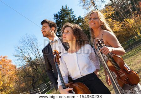 Portrait of three musicians, young people, scene at a farm